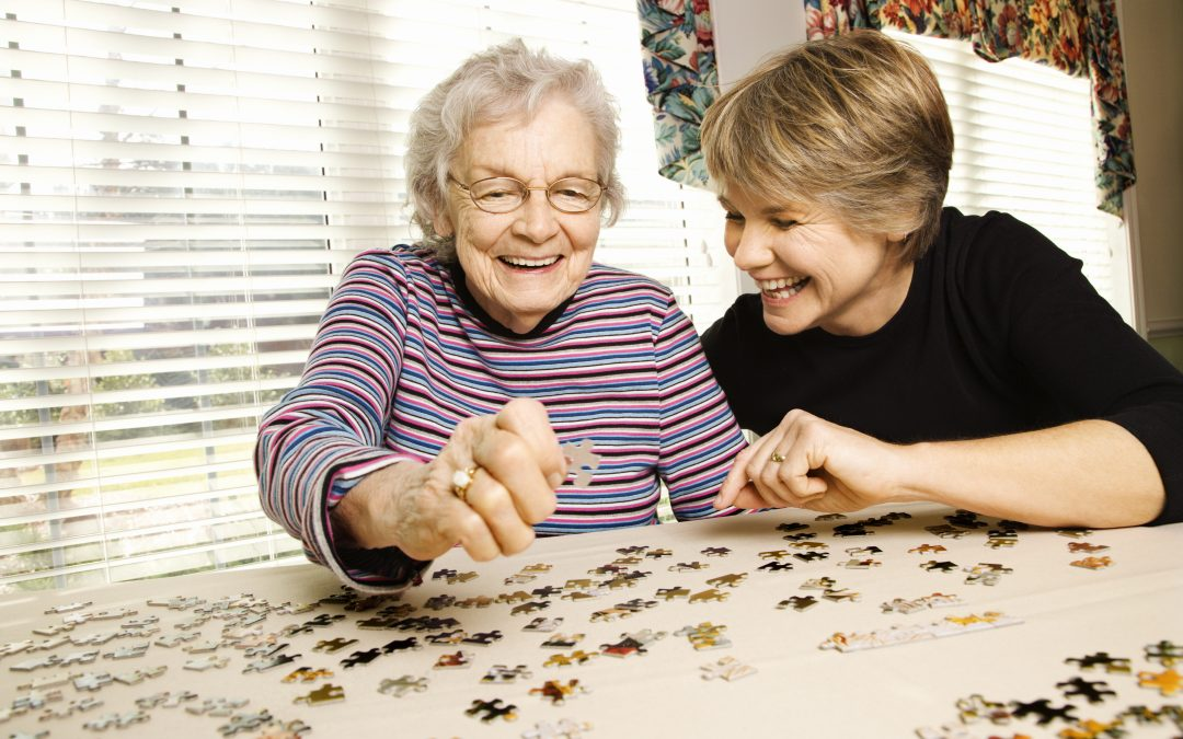 Elderly Woman and Younger Woman Doing Puzzle In Assisted Living Home